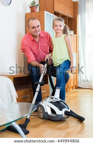 Happy dad and his smiling little daughter hoovering in the living room together