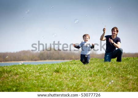 happy dad and his son playing together in the nature with soap bubbles - stock photo