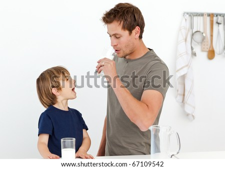 Happy dad and son drinking milk together in the kitchen - stock photo