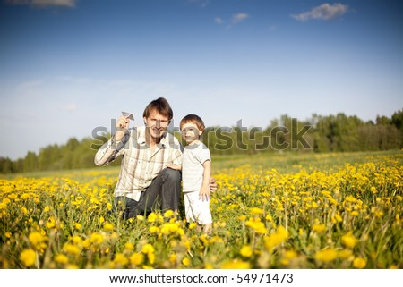 happy dad and son launch paper plane in the field of dandelions - stock photo