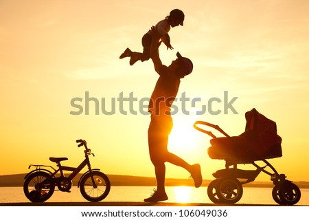 happy dad  daughter throws up into the sky next to the stroller at sunset - stock photo