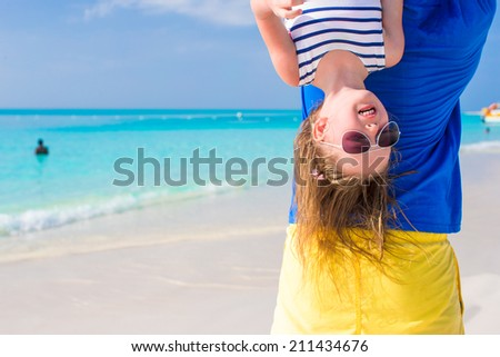 Happy dad have fun with his little cute girl at perfect beach - stock photo