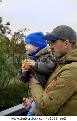 Happy dad holding his son, little funny kid boy on arm, on cold day, walking together in a park in spring, autumn or winter.