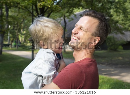 Happy dad holding his son, little funny kid boy on arm, on sunny day, walking together in a park in summer or spring. Happy, joyful family. - stock photo