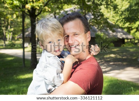 Happy dad holding his son, little funny kid boy on arm, on sunny day, walking together in a park in summer or spring. Happy, joyful family.