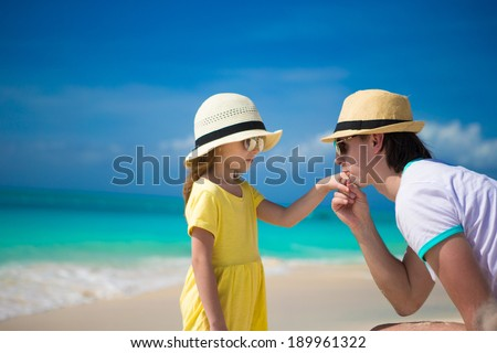 Happy dad kisses the hand of his little daughter on beach - stock photo