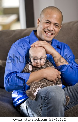 Happy dad with 3 month old baby sitting on lap