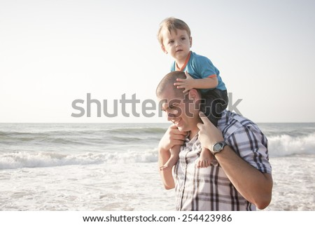 happy dad with young son on shoulders playing at the beach