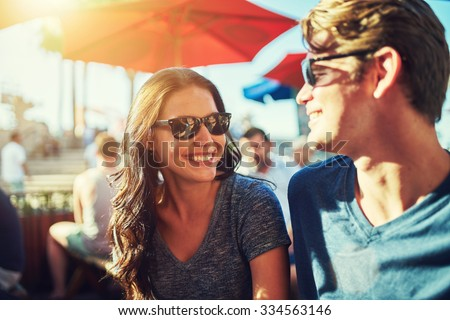 happy dating couple at outdoor restaurant with lens flare and shot with selective focus - stock photo