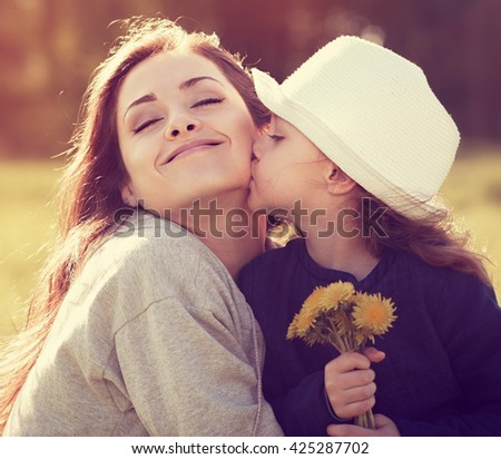Happy daughter kissing her enjoying mother on summer sunny background. Toned closeup portrait - stock photo