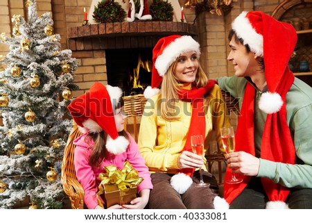 Happy daughter looking at her parents while they cheering up with champagne flutes on Christmas Eve - stock photo