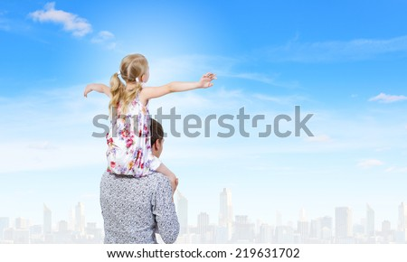 Happy daughter sitting on shoulders of her father - stock photo