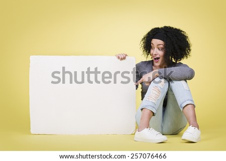Happy delighted girl pointing at a blank white paper sign board with empty copy space, isolated on yellow background. - stock photo