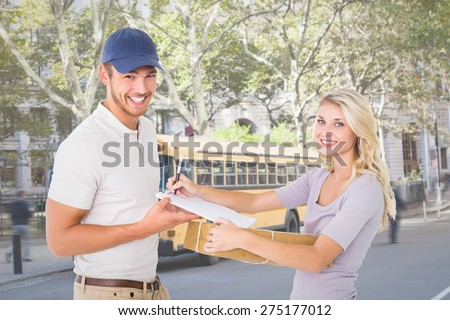 Happy delivery man giving package to customer against schoolbus on ny street - stock photo