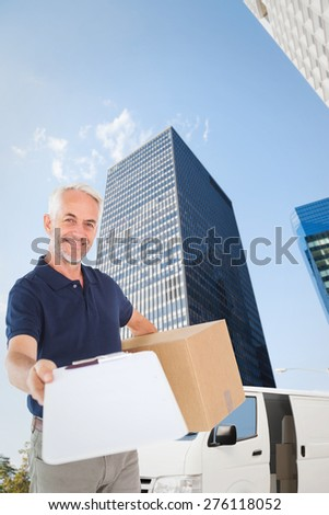 Happy delivery man holding cardboard box and clipboard against skyscraper - stock photo