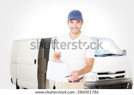 Happy delivery man holding clipboard against white delivery van - stock photo