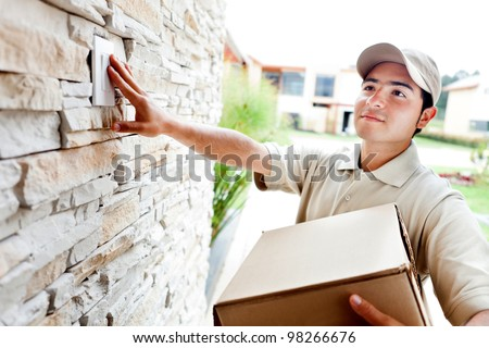 Happy delivery man outdoors ringing house doorbell