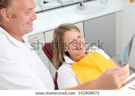 Happy dentist and female patient analyzing Xray in clinic - stock photo
