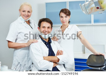 Happy dentist with his dental team in his dental practice