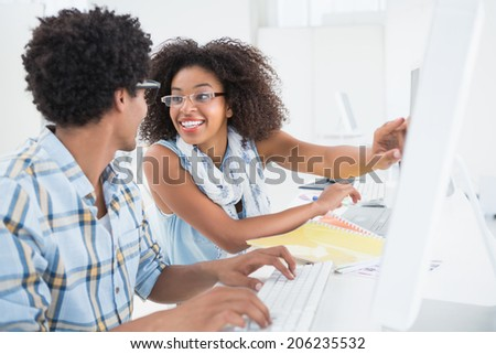 Happy design team working at desk together in their office - stock photo