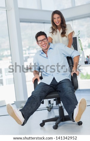 Happy designers having fun with a swivel chair in their office - stock photo