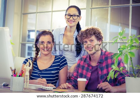 Happy designers smiling at camera in creative office - stock photo