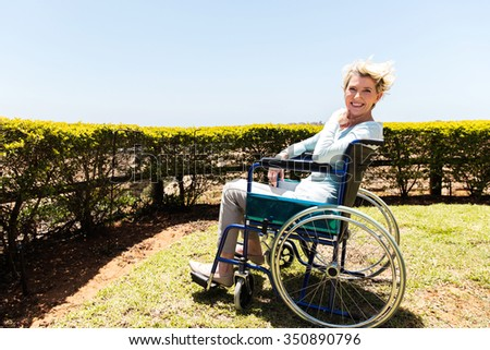 happy disabled middle aged woman sitting outdoors - stock photo