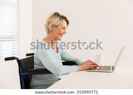 happy disabled senior woman looking at laptop screen - stock photo