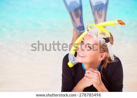 Happy diver woman lying down on beautiful sandy coast, enjoying summer water sport, active lifestyle, joyful vacation on beach resort - stock photo