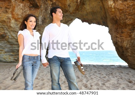 Happy diverse attractive man and woman couple walking on the beach in love - stock photo