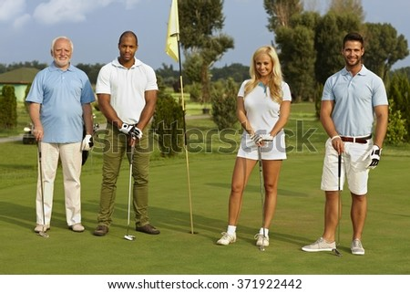 Happy diverse companionship standing on the green, ready to play, smiling, looking at camera. - stock photo