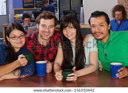Happy diverse group of friends with coffee in cafe - stock photo