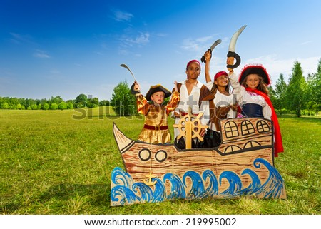 Happy diversity children as pirates with swords - stock photo