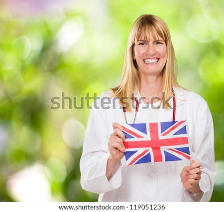 Happy Doctor Holding British Flag against a nature background