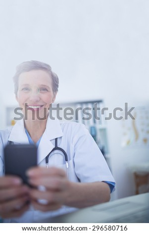 Happy doctor looking at camera and using her smartphone in medical office - stock photo