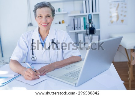 Happy doctor looking at camera and writing on clipboard in medical office - stock photo