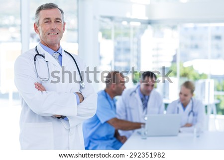 Happy doctor looking at camera with arms crossed while his colleagues works in medical office - stock photo