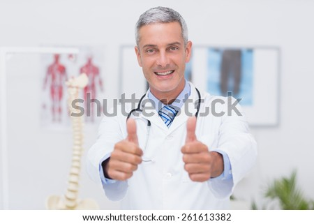Happy doctor looking at camera with thumbs up in medical office - stock photo