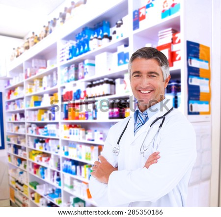 Happy doctor smiling at camera against close up of shelves of drugs - stock photo