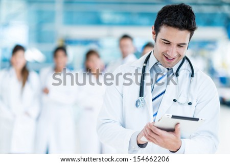 Happy doctor using tablet computer at the hospital  - stock photo