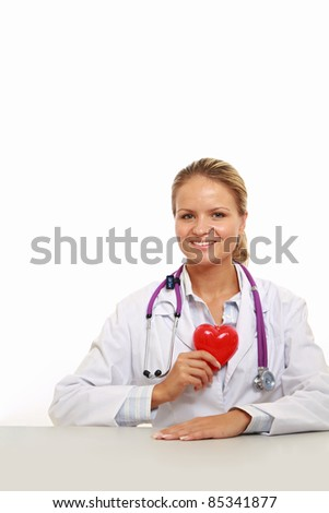 Happy doctor with red heart symbol at desk isolated - stock photo