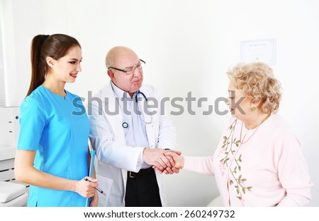 Happy doctors and patients in hospital clinic - stock photo