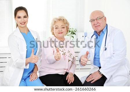 Happy doctors and patients in hospital clinic