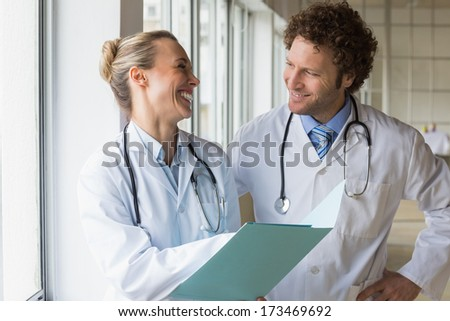 Happy doctors discussing over file on hospital - stock photo