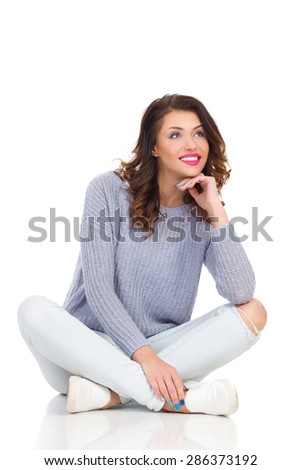 Happy Dreamer Girl. Smiling young woman in sweater and jeans sitting on a floor with legs crossed, holding hand on chin and looking away. Full length studio shot isolated on white. - stock photo