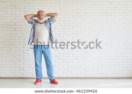 Happy dreaming dressed fashionably standing and holding his hands behind his head, white brick wall in background