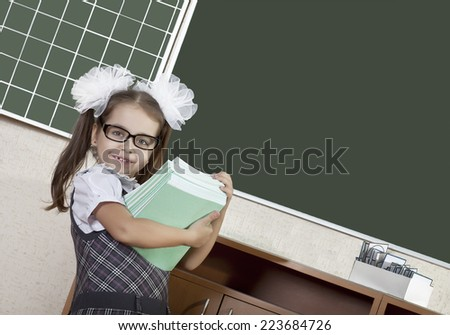 Happy duty schoolgirl with a pile of books at the blackboard - stock photo