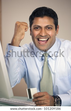 Happy East Indian businessman with cheering fist pump celebrating success while holding a credit card - stock photo