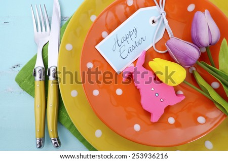 Happy Easter bright color orange, yellow and green polka dot theme table place setting with pink fondant bunny cookie and tulips on pale aqua blue distressed wood table. - stock photo