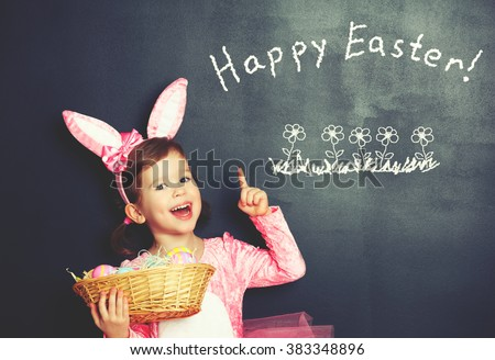 Happy Easter! child girl in costume bunny rabbit with ears and  basket of eggs about blackboard